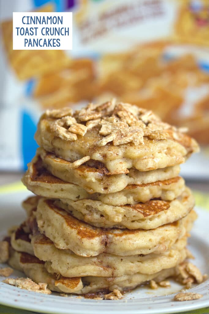 Head-on view of a stack of Cinnamon Toast Crunch pancakes topped with the cereal with the box in the background and recipe title at top
