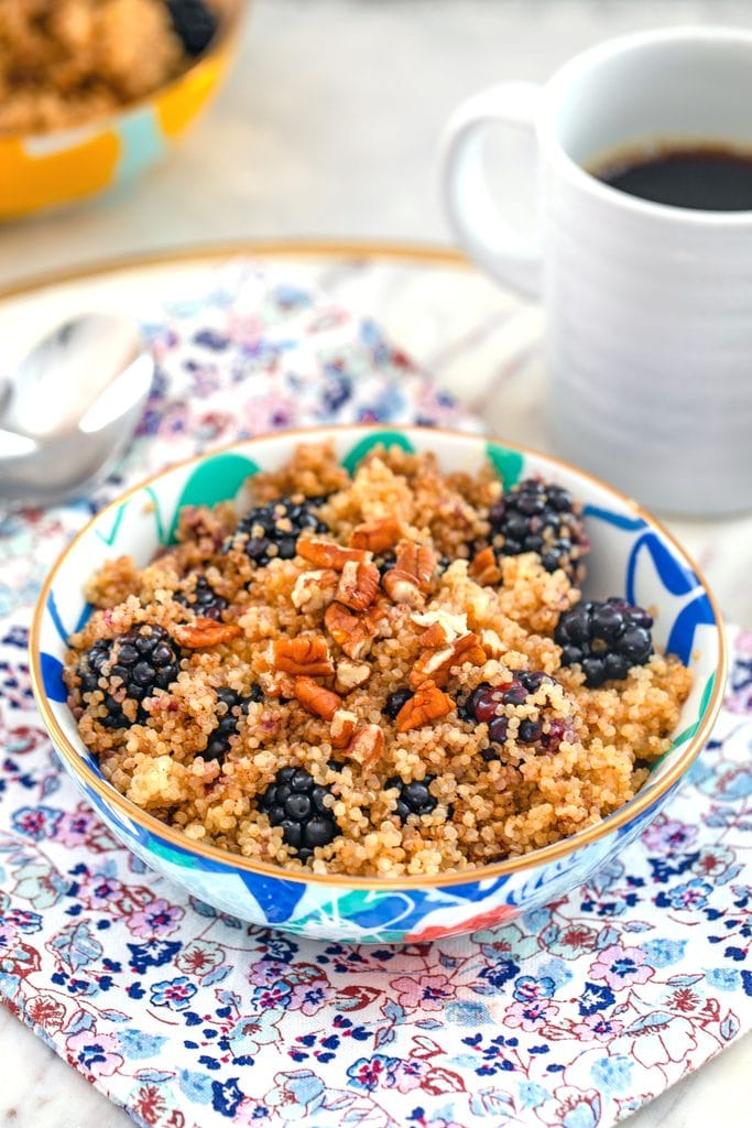 Head-on view of colorful bowl of cinnamon and blackberry breakfast quinoa topped with pecans on a flowered towel with cup of coffee and spoon in the background