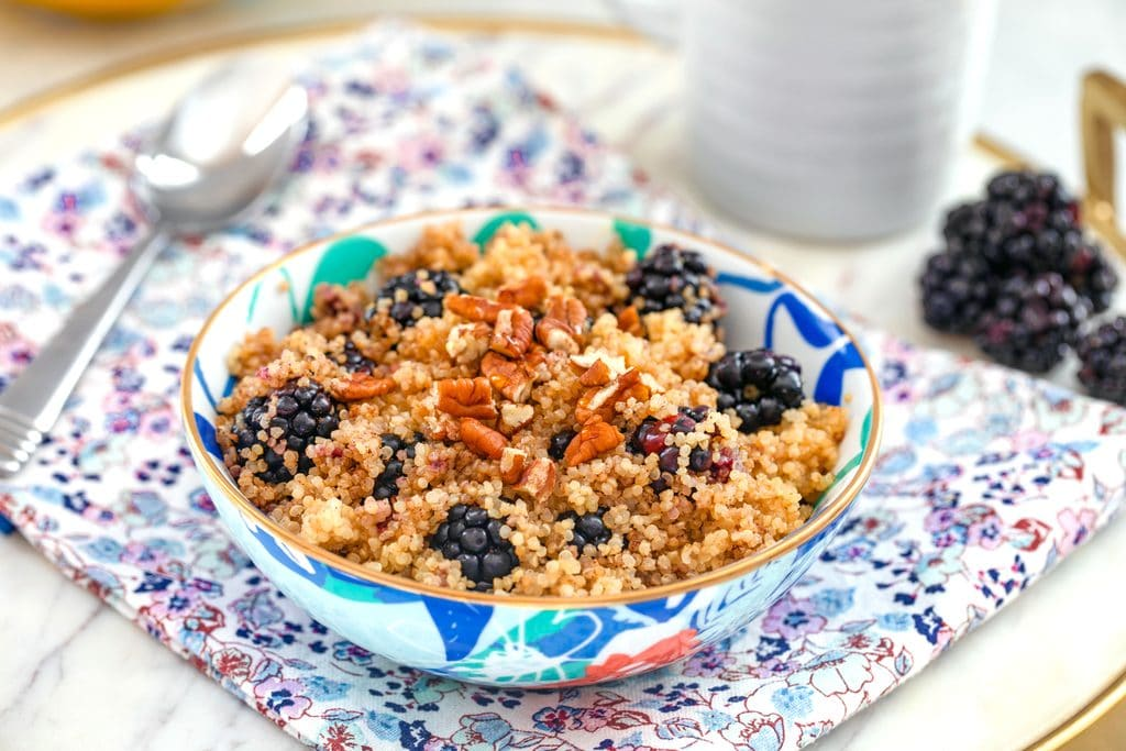 Landscape photo of colorful bowl of cinnamon and blackberry breakfast quinoa topped with pecans on flowered towel with spoon, blackberries, and mug in the background