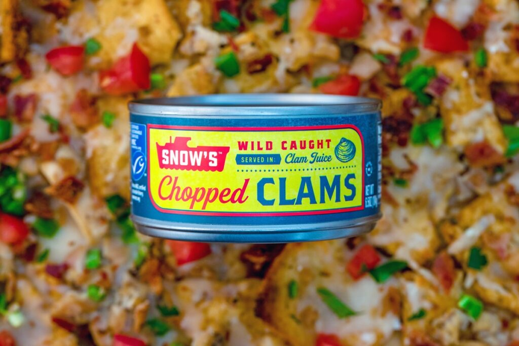Can of chopped clams sitting over a platter of clam nachos