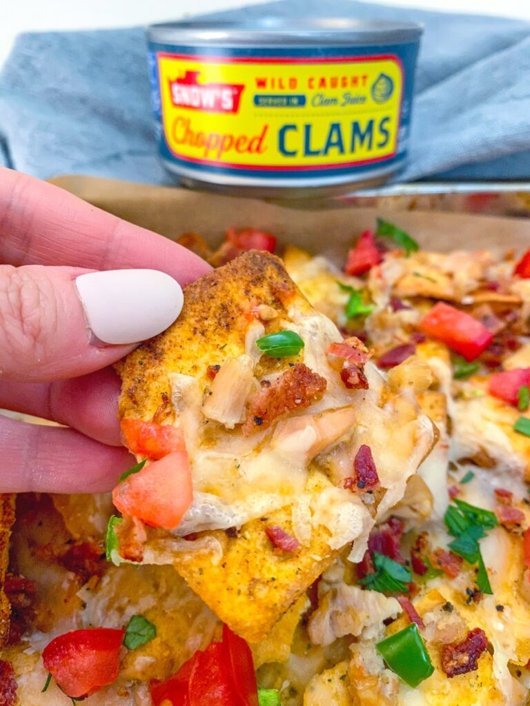 Hand holding up a clam nacho with can of chopped clams in the background