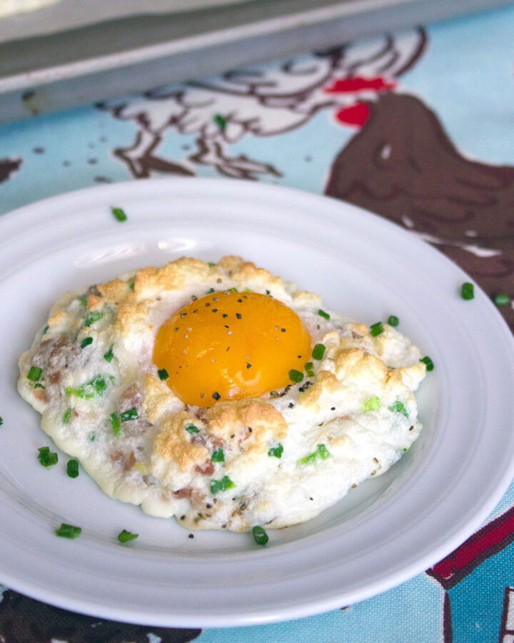 Head-on view of a cloud egg with cheddar, prosciutto, and jalapeño on a white plate