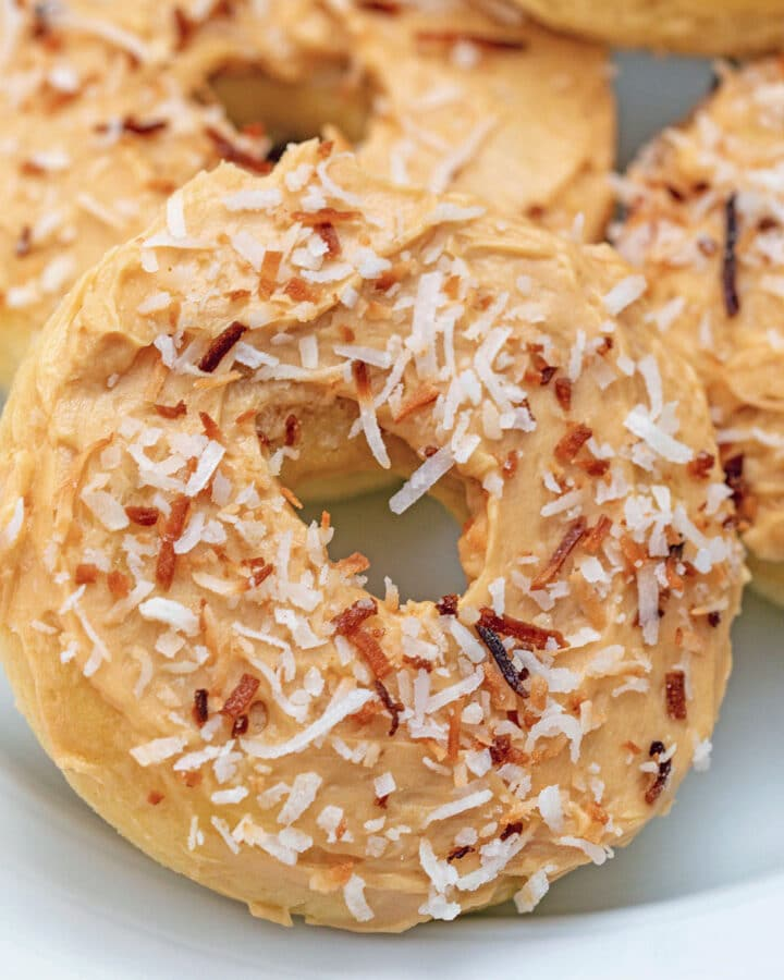 Close-up view of a coconut doughnuts with salted caramel icing and toasted coconut on top