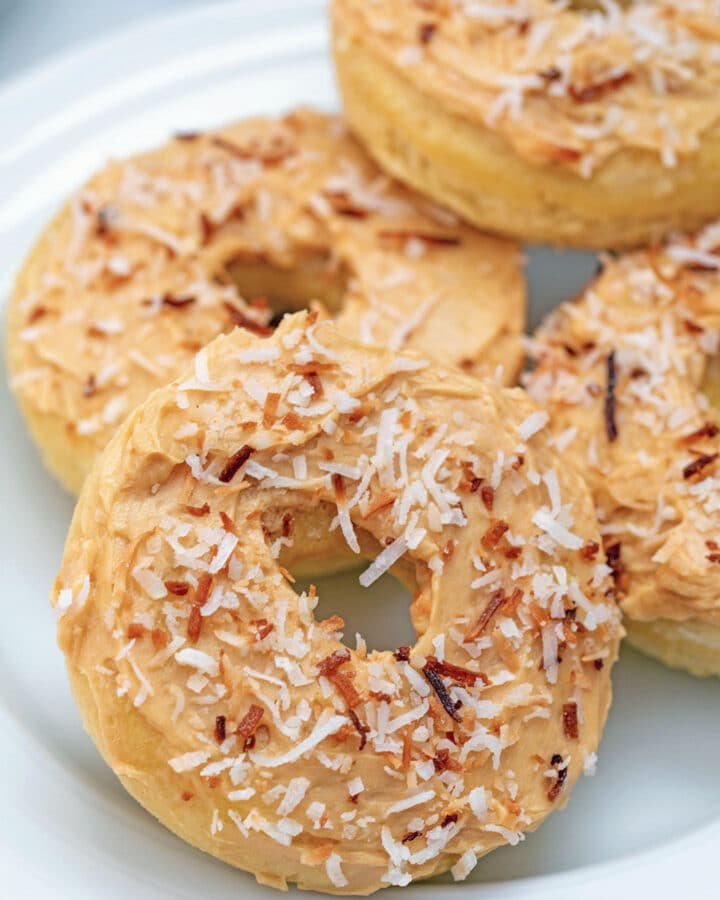 Close-up view of a coconut doughnut with salted caramel icing and toasted coconut with more doughnuts in background