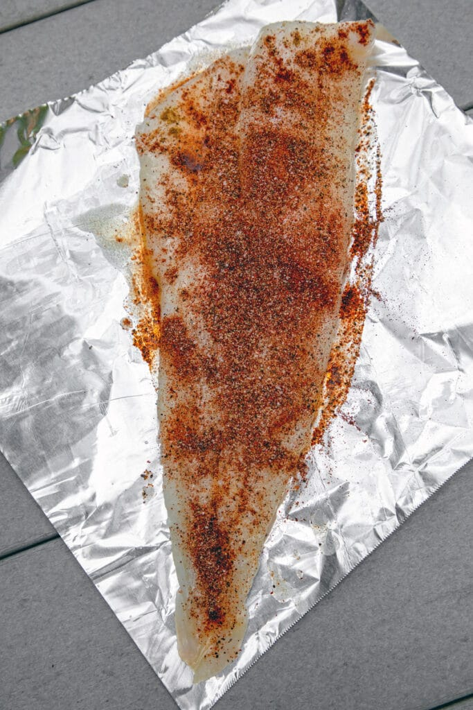 Overhead view of piece of cod coated in spices