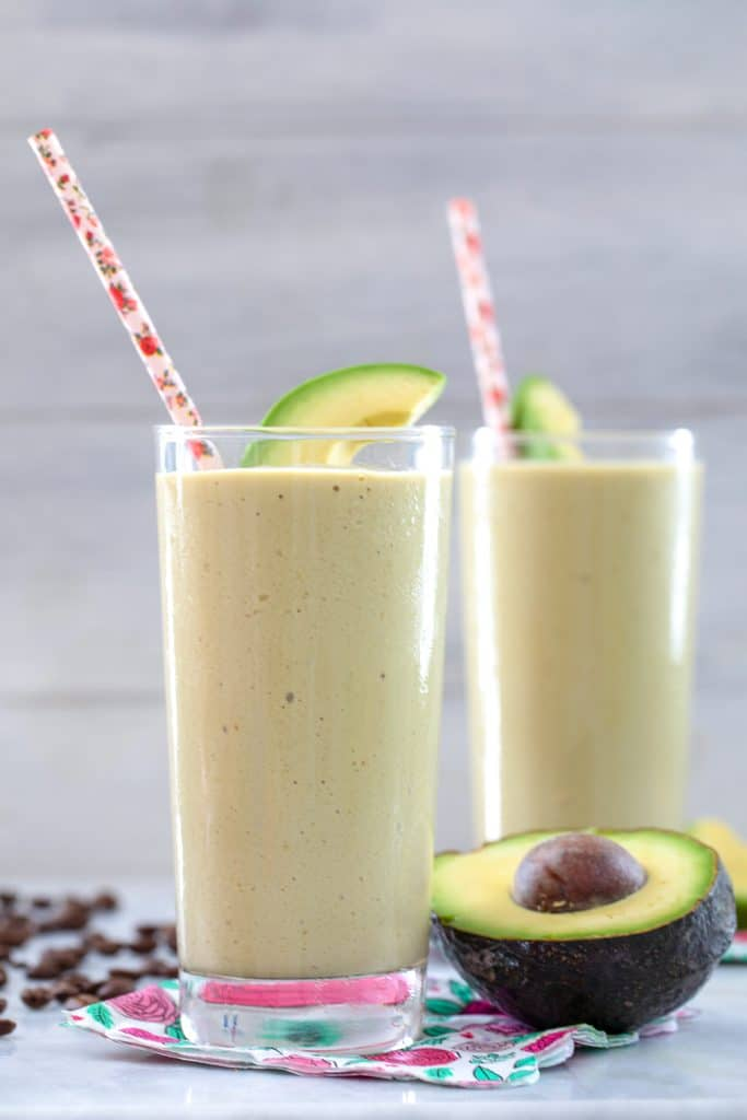 Up close head-on view of coffee avocado milkshake in a tall glass with pink straw and avocado garnish and another glass, avocado half, and coffee beans in the background