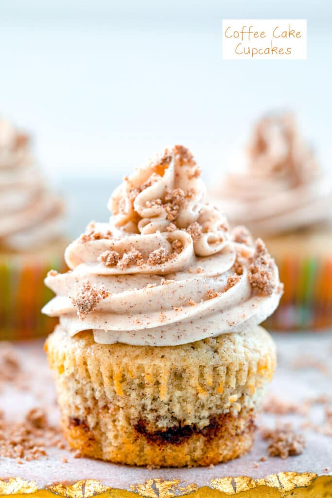 Head-on close-up view of a coffee cake cupcake with cinnamon swirl, cinnamon frosting and crumb topping with recipe title at top