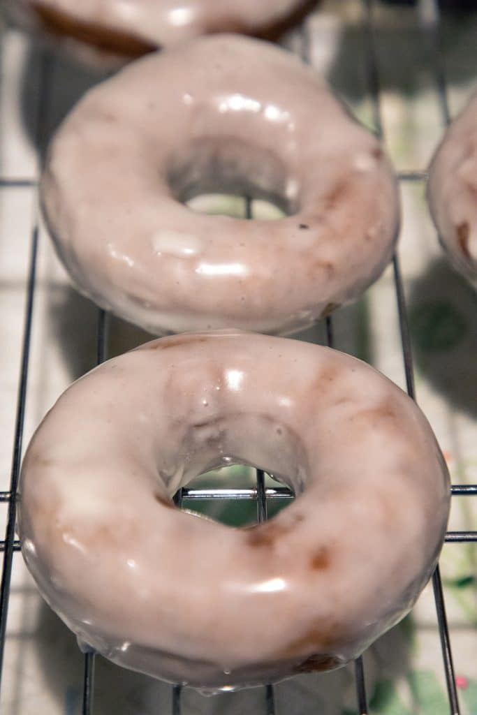 Coffee flavored donuts with glaze resting on cooling rack