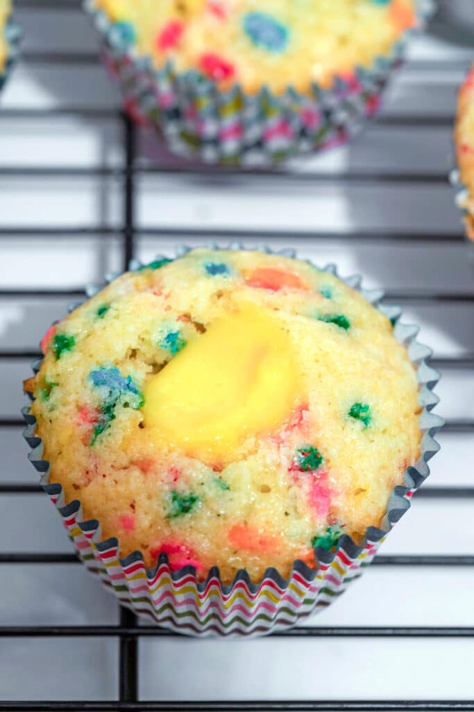 Confetti cupcakes on cooling rack being filled with champagne custard