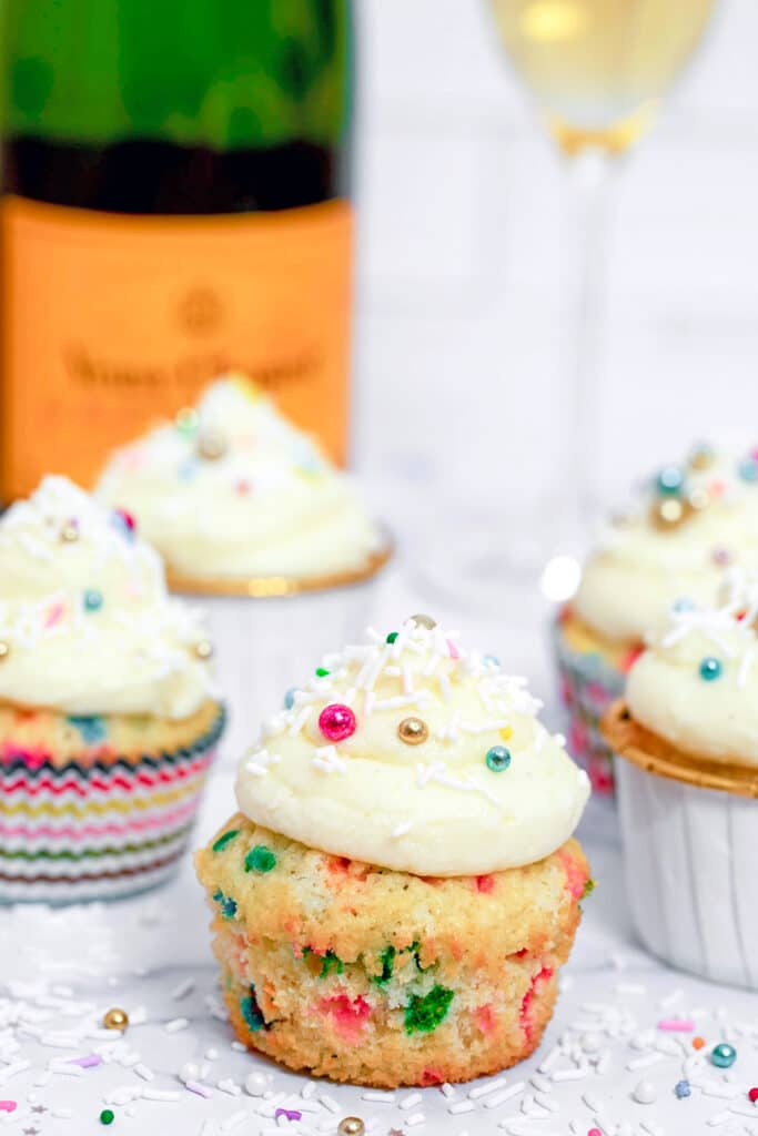 Head-on view of confetti cupcake with champagne custard and champagne buttercream with more cupcakes, sprinkles, champagne bottle, and champagne glass in background