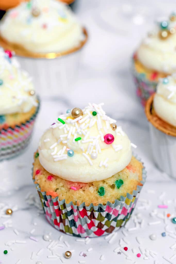 Head-on closeup view of a confetti cupcake with champagne custard and buttercream with lots of sprinkles