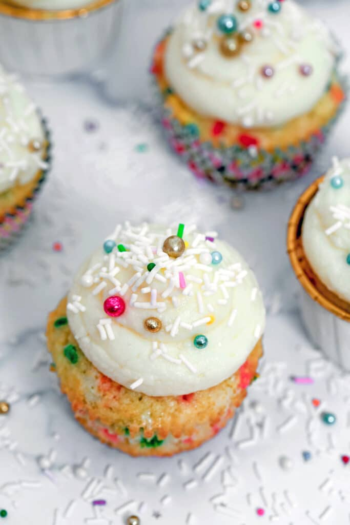 Overhead view of confetti cupcakes with champagne custard and frosting with sprinkles all around