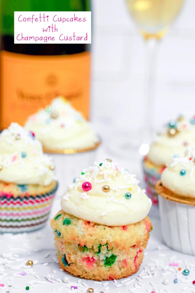 Head-on view of confetti cupcake with champagne custard and champagne buttercream with more cupcakes, sprinkles, champagne bottle, and champagne glass in background with recipe title at top