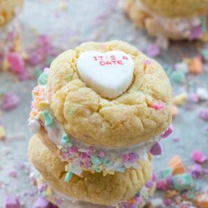 Conversation Heart Cookies with Marshmallow Fluff -- Put those conversation hearts to good use this Valentine's Day by baking Conversation Heart Cookies. Marshmallow fluff is sandwiched between two colorful candy confetti-packed sugar cookies and will instantly have you falling in love | wearenotmartha.com