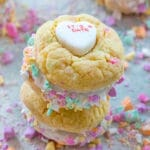 Two conversation heart sandwich cookies with fluff stacked on each other with crushed conversation hearts all around