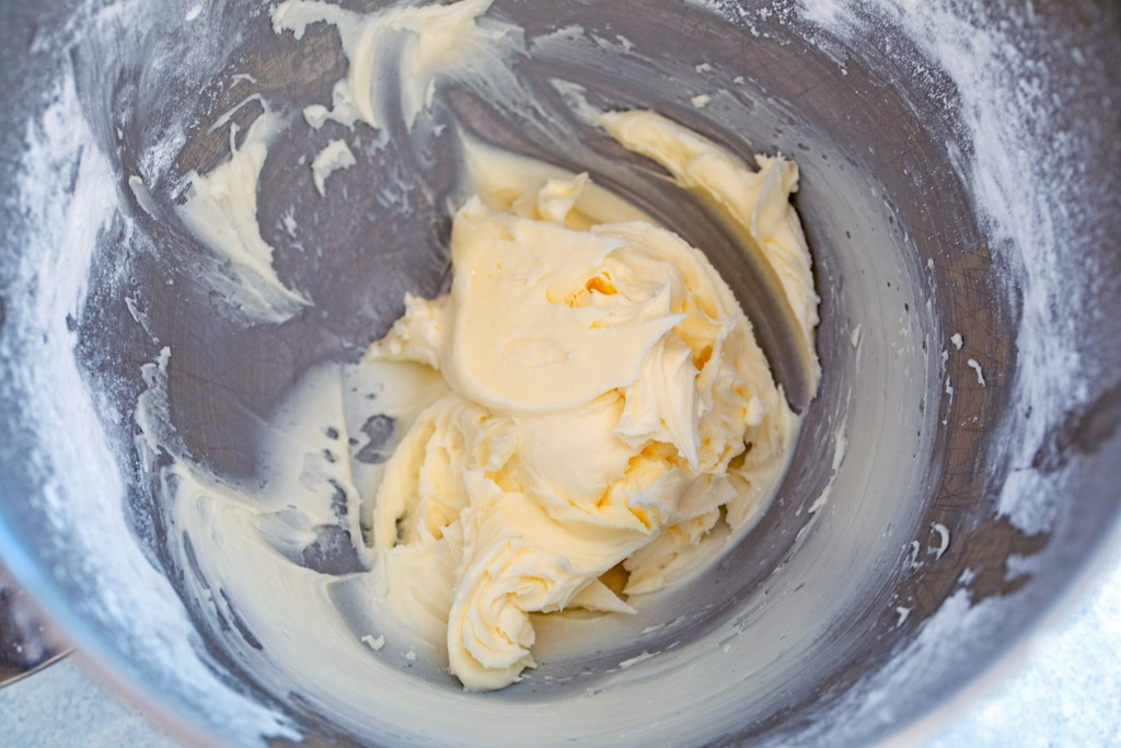 Overhead view of buttercream icing in mixing bowl.