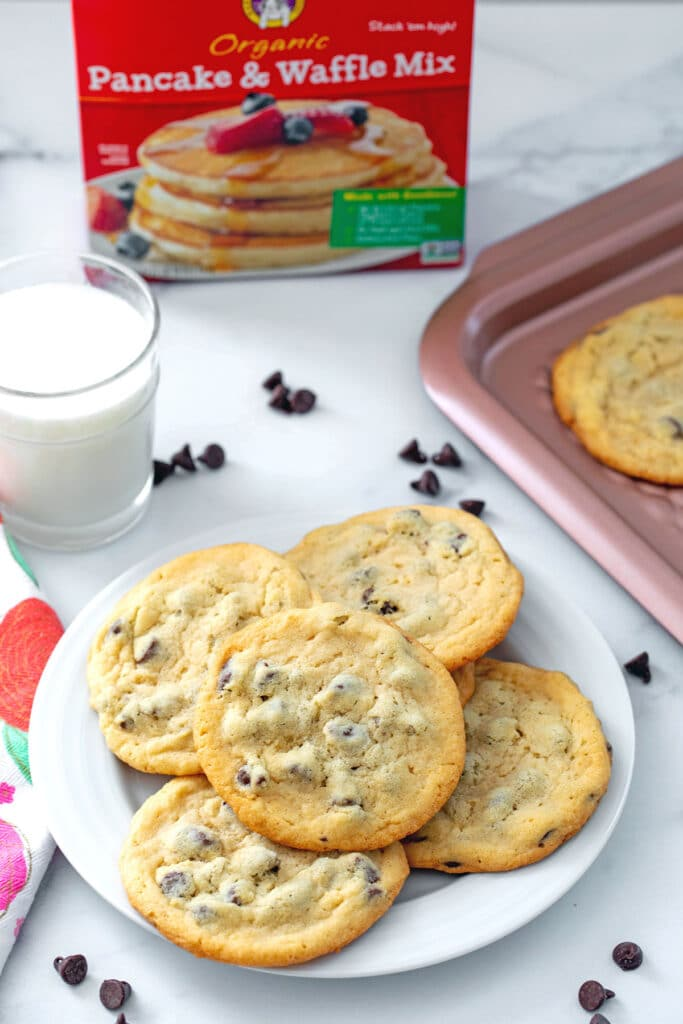 Overhead view of plate of chocolate chip cookies made with pancake mix with cookies, chocolate chips, glass of milk, and box of pancake mix in background