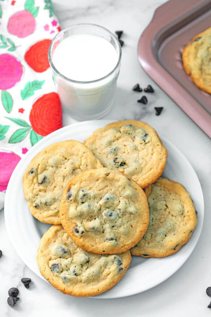 Overhead view of a plate filled with chocolate chip cookies with pancake mix with a glass of milk, chocolate chips, and cookie sheet in the background