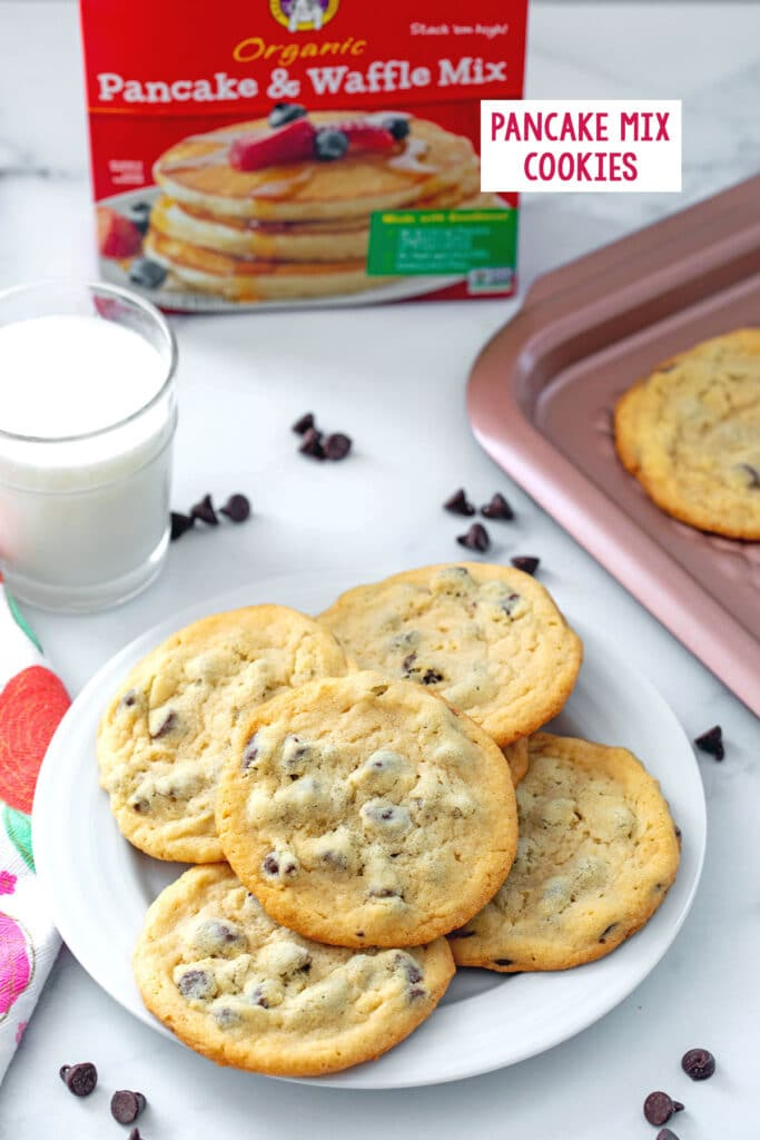 Overhead view of plate of chocolate chip cookies made with pancake mix with cookies, chocolate chips, glass of milk, and box of pancake mix in background and recipe title at top