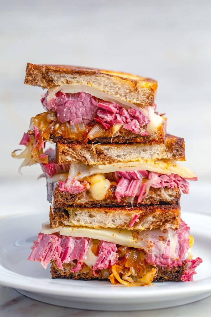 Head-on view of corned beef melts stacked on a white plate