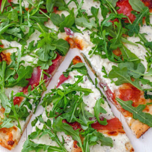 Cottage cheese and pizza are a match made in heaven! This Cracked Pepper Cottage Cheese Pizza with Prosciutto and Arugula makes a delicious anytime dinner, but can also be served as a party appetizer.