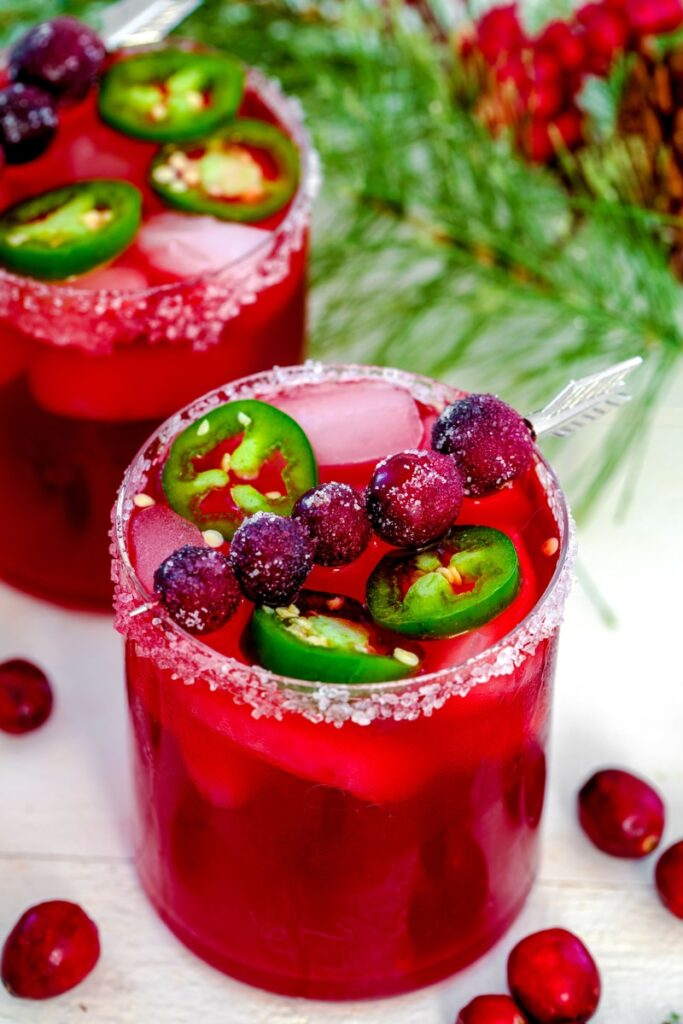 Close-up view of cranberry jalapeño margarita with sugared cranberries and jalapeño round garnish with holiday holly in background