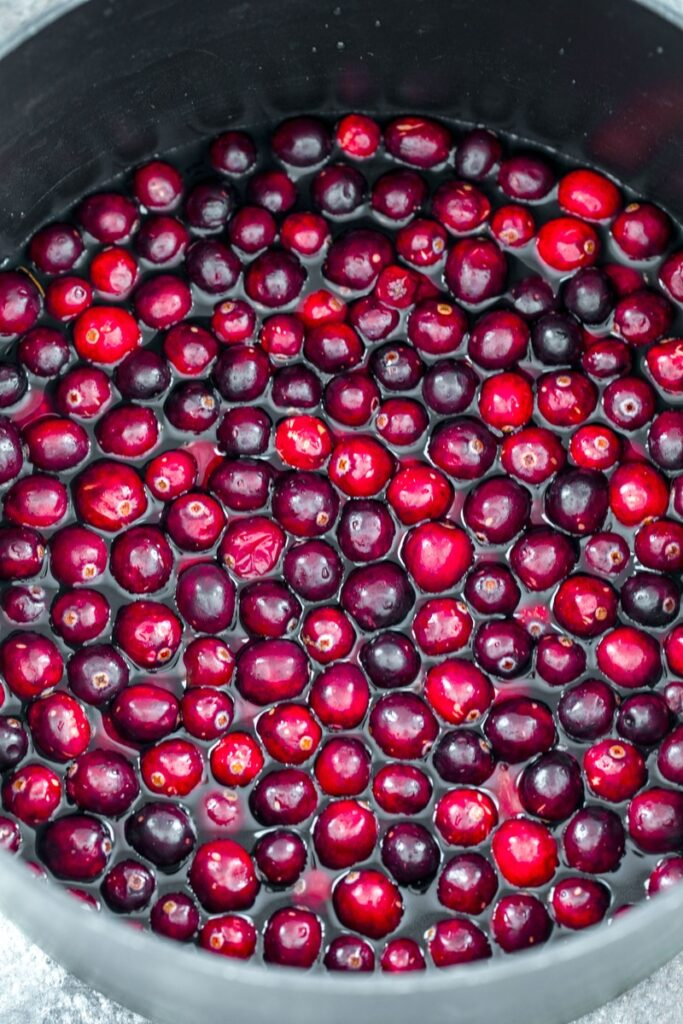 overhead view of cranberries in stockpot of water