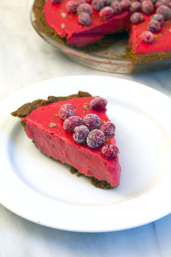 Head-on view of a slice of cranberry lime pie topped with sugared cranberries and lime zest on a white plate with remaining pie in the background