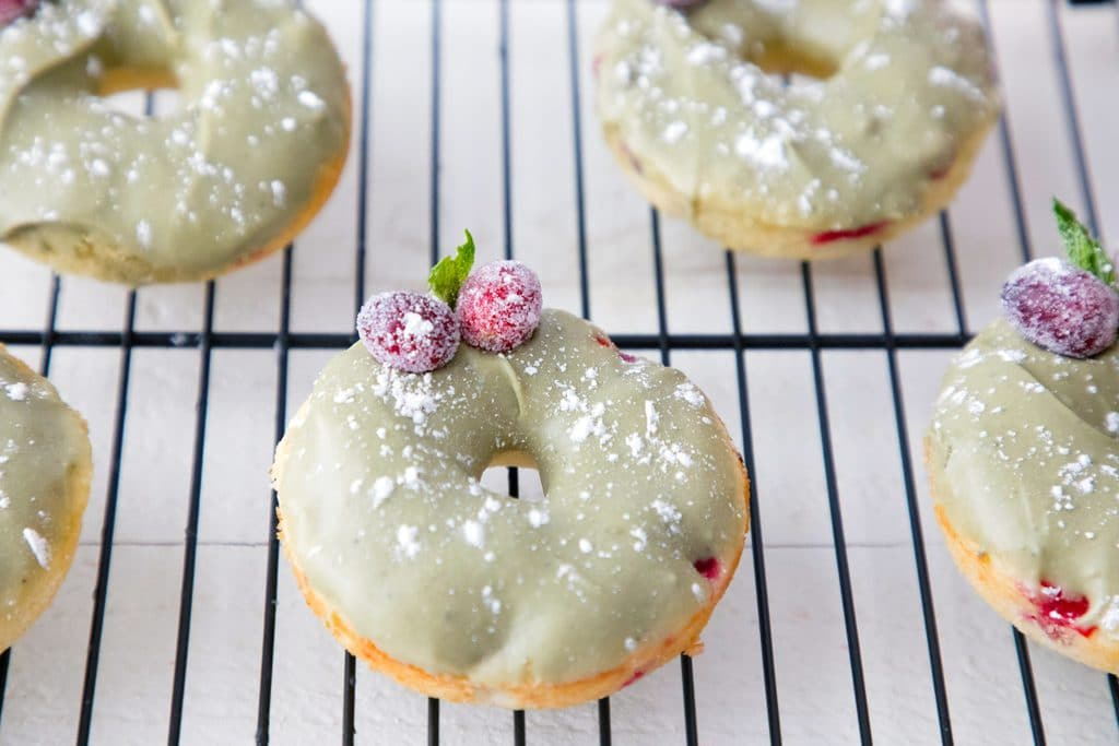 Landscape view of multiple cranberry matcha donuts on baking rack