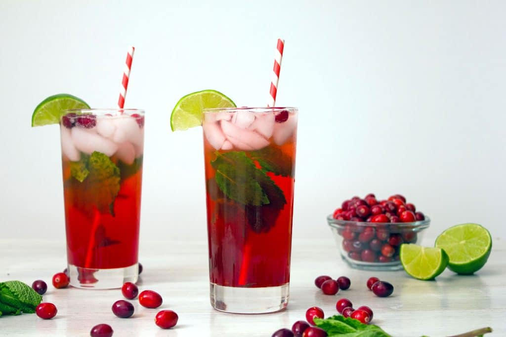 Landscape photo of two cranberry mojitos with lime wedge and cranberry garnish with red and white straws with cranberries, mint leaves, and limes scattered around background
