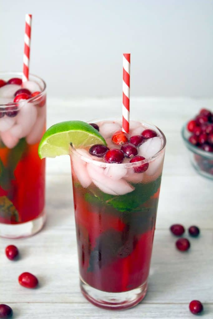Head on view of cranberry mojito in tall glass with cranberry, mint, and lime garnish and red and white striped straw with second cocktail and cranberries in background