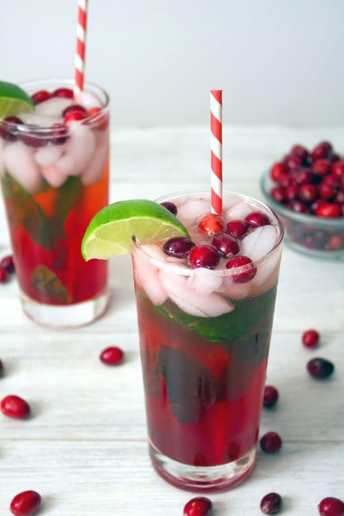 Overhead view of two cranberry mojitos garnished with a lime wedge and cranberries with red and white striped straws and cranberries scattered around