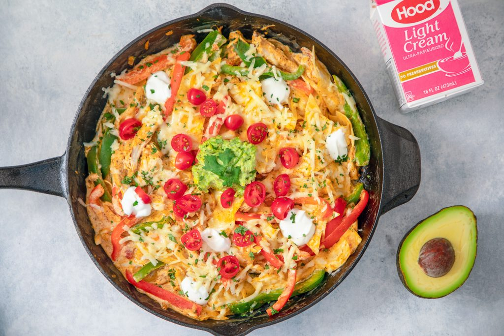 Landscape view of creamy fajita skillet with tomatoes, cheese, guacamole, and cilantro with avocado half and cream container in background
