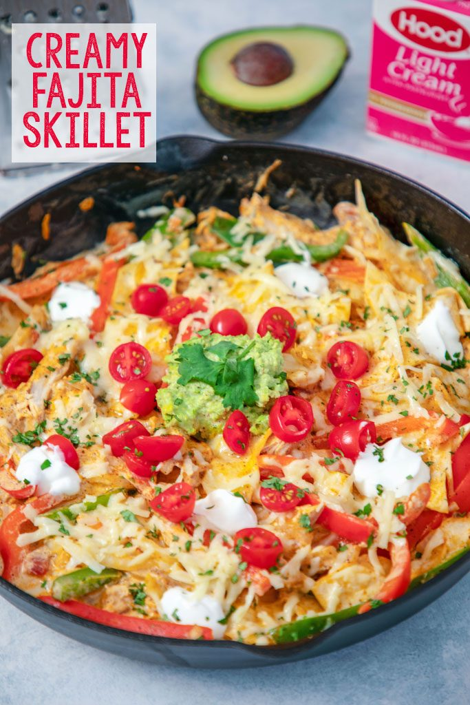 "Overhead view of fajita skillet with tomatoes, cheese, guacamole, and cilantro with half an avocado and cream container in the background and ""Creamy Fajita Skillet"" text at top"