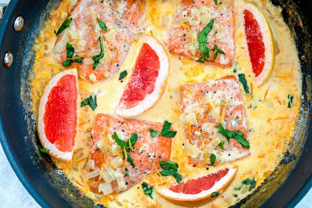 Landscape view of a skillet with creamy grapefruit salmon, including salmon filets, grapefruit wedges, chopped onions, basil, and a grapefruit cream sauce