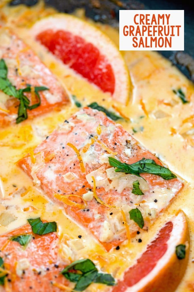 Overhead closeup view of creamy grapefruit salmon in a skillet with basil, grapefruit wedges, and a grapefruit cream sauce with recipe title at top