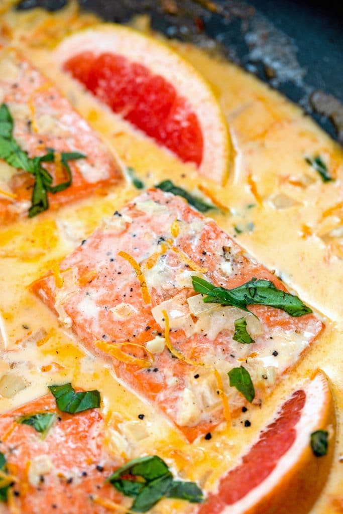 Overhead closeup view of creamy grapefruit salmon in a skillet with basil, grapefruit wedges, and a grapefruit cream sauce