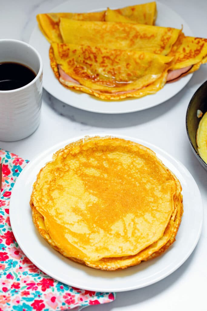 Stack of crepes with pancake mix on plate with three ham and cheese crepes, crepe pan, and cup of coffee in the background