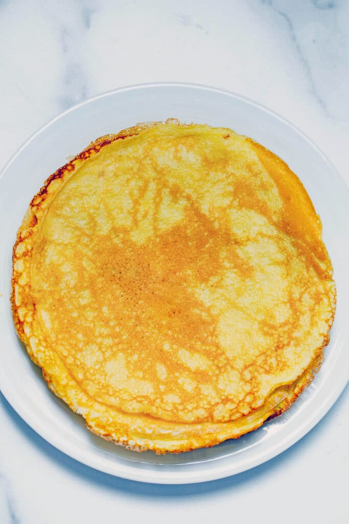 Overhead view of a stack of crepes with pancake mix