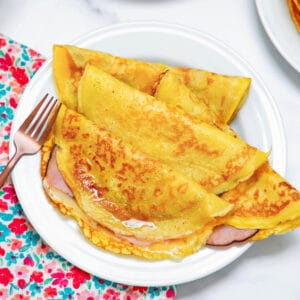 View of multiple ham and cheese crepes made with pancake mix on a white plate