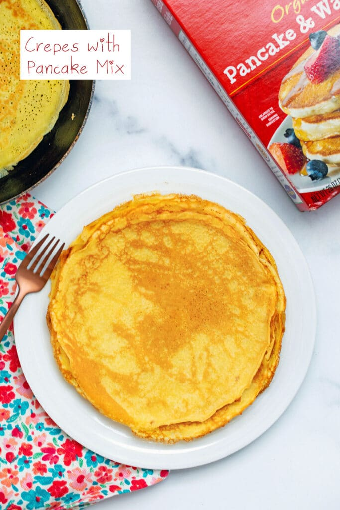 Overhead view of a plate with a stack of crepes made with pancake mix, a crepe cooking in a pan, and a box of pancake mix with recipe title at top