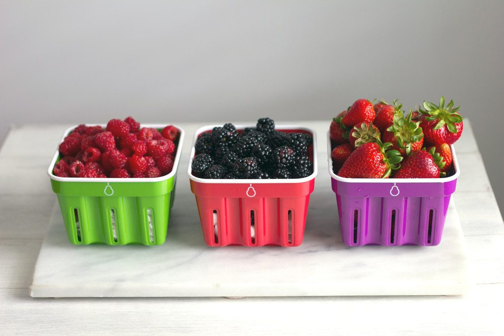 Raspberries, blackberries, and strawberries in Crisp brand berry baskets all in a row