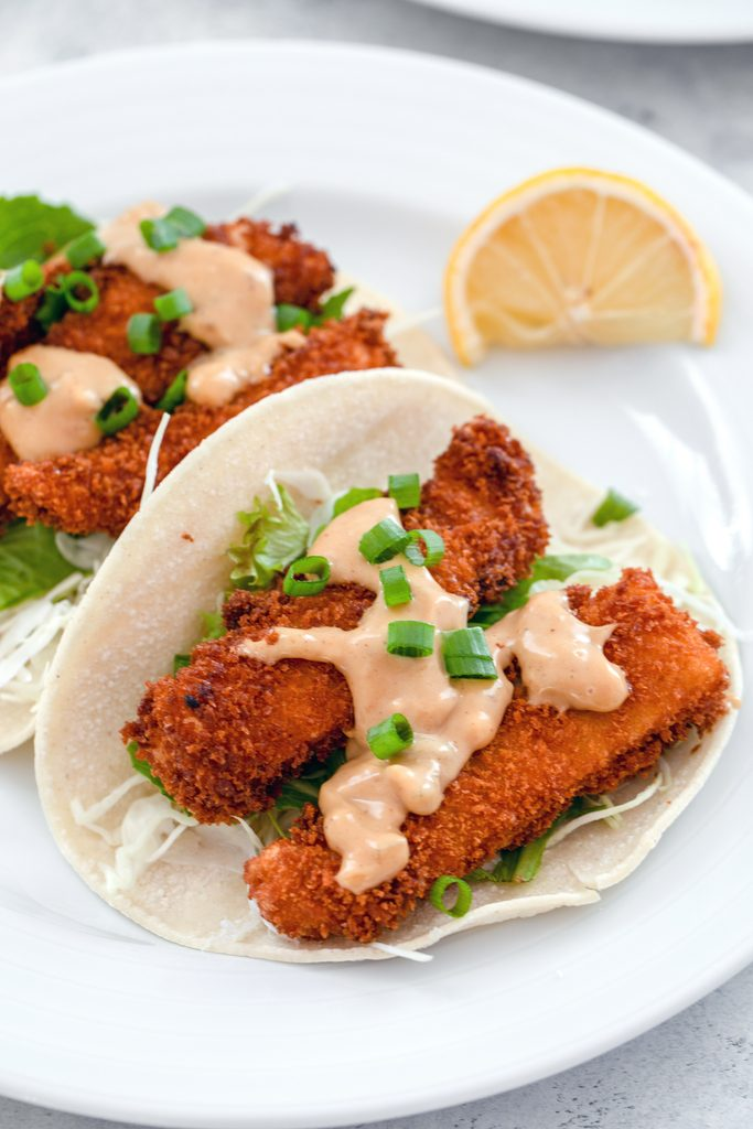 Overhead view of a white plate with two fried fish tacos with hoisin mayo and scallions with a lemon wedge on the side