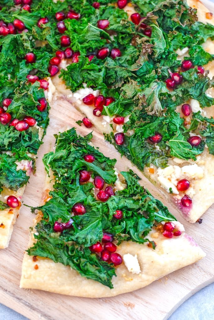 Overhead view of kale flatbread topped with crispy kale, feta, and pomegranate arils with a slice pulled out from rest of pizza