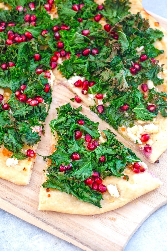 Overhead view of kale flatbread pizza topped with kale, feta, and pomegranate on a wooden board with one slice pulled out