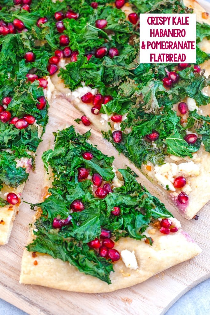 Overhead view of kale flatbread topped with crispy kale, feta, and pomegranate arils with a slice pulled out from rest of pizza and recipe title at top