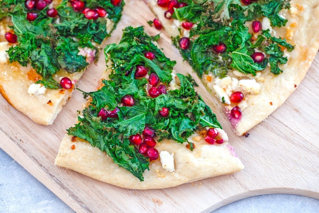 Landscape closeup image of slice of kale flatbread pizza with pomegranate and habanero being pulled out from rest of pizza on wooden board