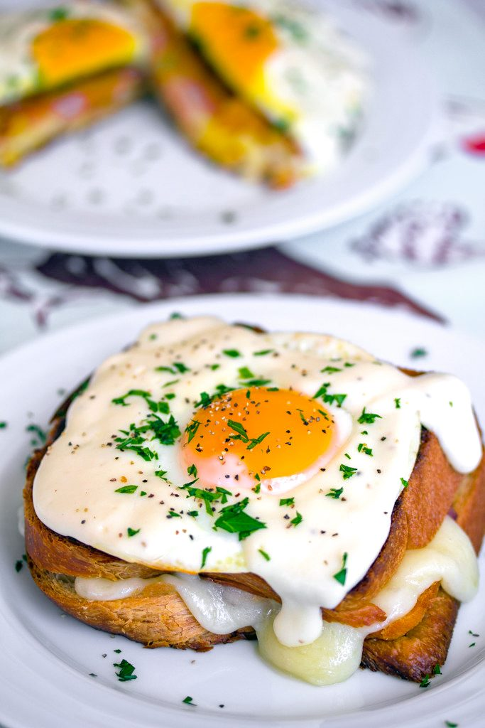 Head-on view of a croque madame with egg, mornay sauce, and parsley on a white plate with a second sandwich in the background and recipe title at top