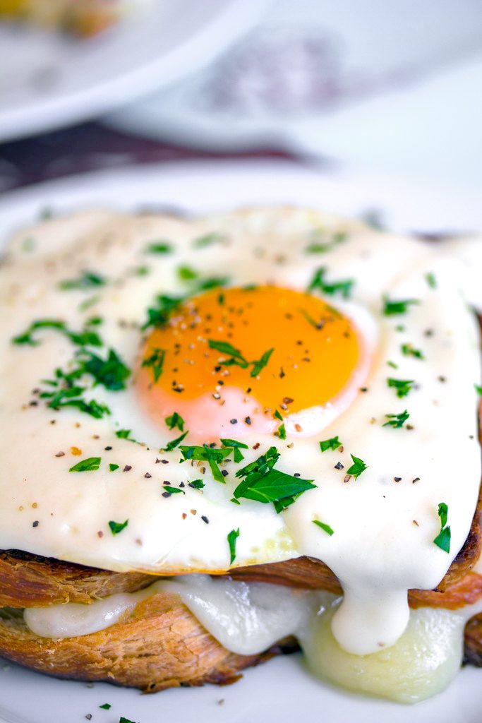 Overhead close-up view of a croque madame with perfectly cooked egg on top, mornay sauce, and chopped parsley with cheese oozing out
