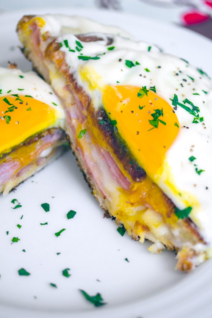 Overhead close-up view of a croque madame with egg on top cut in half